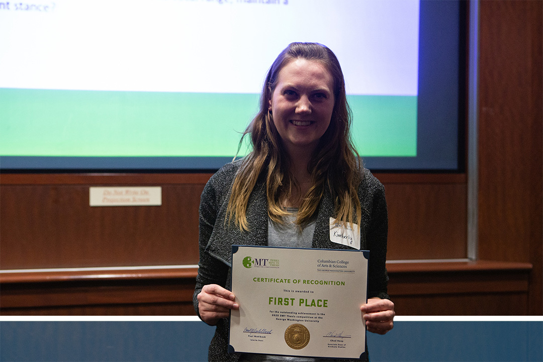 PhD student Kimberly Foecke holds up her 3MT certificate