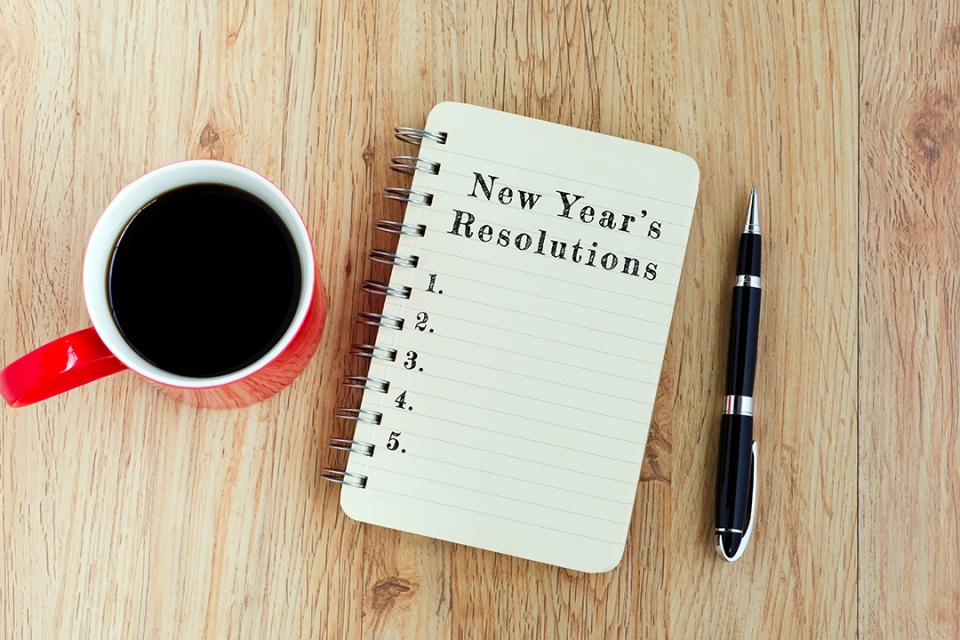 """A coffee cup and a notepad with the text """"New Year's Resolutions"""" written on it"""