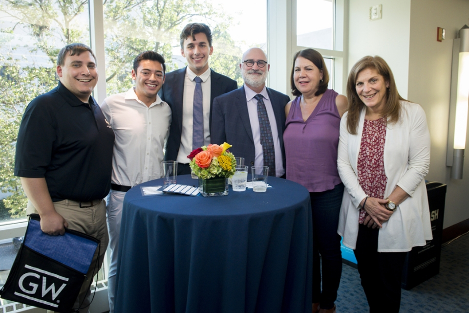 A group of alumni pose at a table