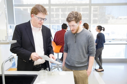 Christopher Cahill (left) in his Science and Engineering Hall lab with PhD chemistry student researcher August Ridenour