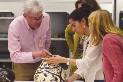 A Smithsonian expert helps decorative arts and design history students examine ceramic and earthenware objects