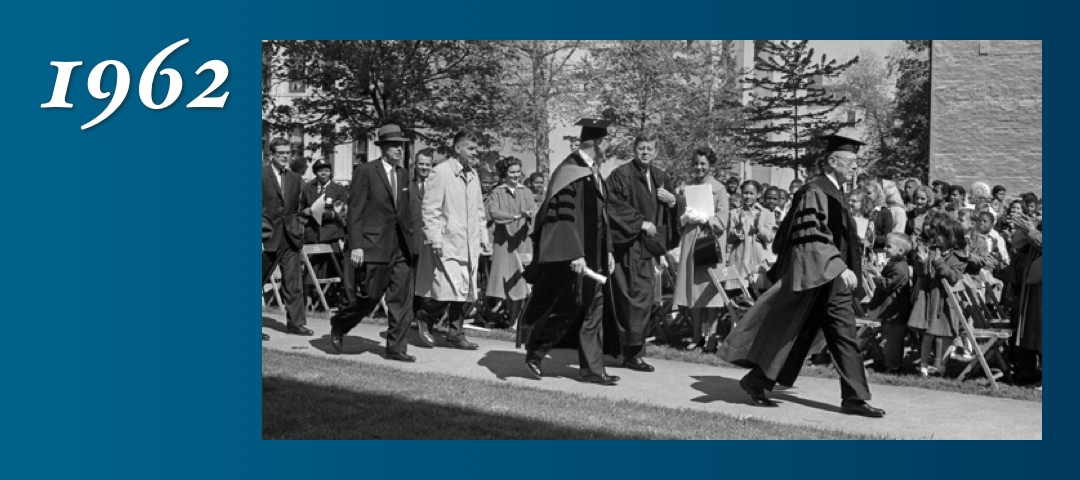 1962: President John F. Kennedy, wearing a graduation gown, and First Lady Jacqueline Kennedy visit GW campus